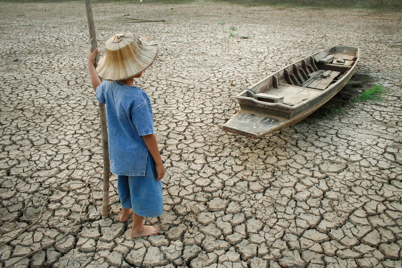 Klimawandel-Fakten-Junge-im-ausgetrockneten-See-mit-Boot